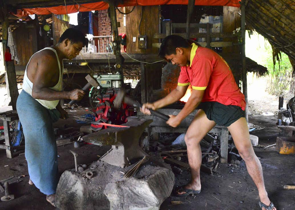 Workers of blacksmith workshop focusing on poduction of agricultural tools in traditional ways at a village in Kawa Township to survive their livelihoods while agricultural machinery are bieng used on a wider scale in rural area for cultivation of paddy and crops.—Photo: Aye Min Soe