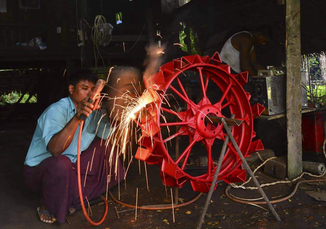 A worker of blacksmith welding a machine part of power-tiller at the workshop in Kawa Township.—Photo: Aye Min Soe
