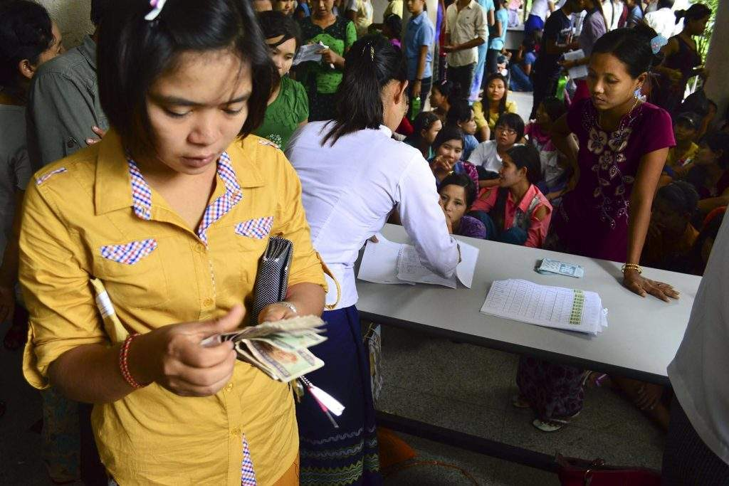 Staff of Master Sports Factory pay salary to workers at the factory in Hlinethaya Industrial Zone.—Photo: Aye Min Soe