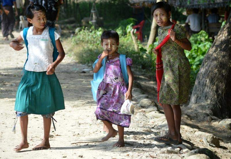 SCHOOL BEGINS SOON: Three schoolgirls are seen on their way to school in Ngwetaung village in Maungtaw Township, Rakhine State. The ethnic Rakhine village is the one that could manage to escape from an arson attack during communal strife between the two communities in the township two years ago.