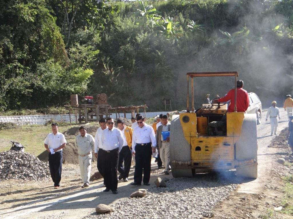 Union Minister for Construction U Kyaw Lwin inspects repaving of road during his tour of Magway Region. mna