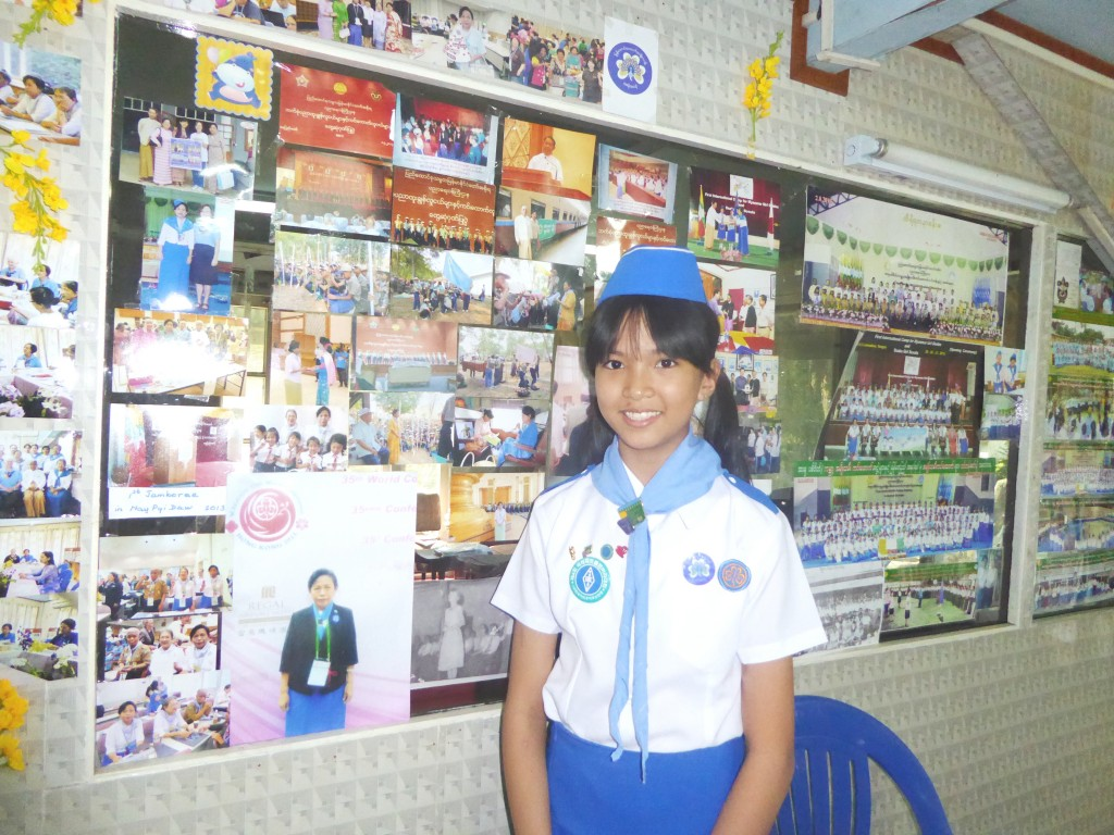 Scout Aye Phone Pyaw Cho, who is a Grade-7 student from Basic Education High School No.2 in Kamayut, seen with documentary photos of Myanmar Girl Guides at the background. Photo: Khaing Thanda Lwin