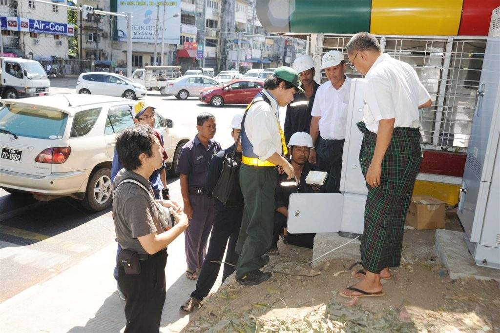 Officials inspect trial run of traffic lights with Japanese technology which uses centralized traffic control system at a junction in Yangon. Photo: Saw Thein Win