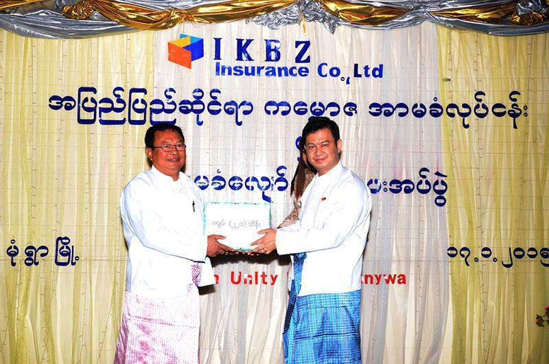 An official of International Kanbawza Insurance Co., Ltd (IKBZ) presents compensation for insurance to U Maung Maung of Monywa Industrial Zone.—MNA
