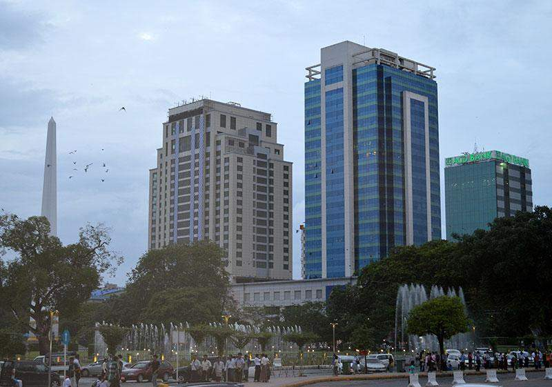 Photo of a view of downtown Yangon showing high-rise buildings and  Independence  Monument.