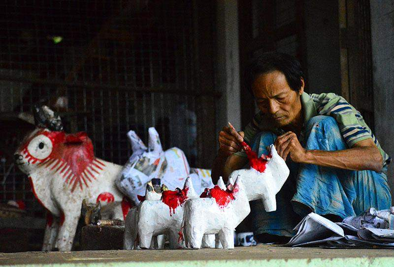 U Kyin Soe paints small-sized cow toys to supply to his customer who place an order for 200 toys from him.