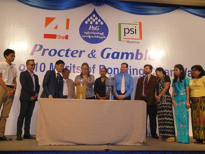 Officials from P&G Co, PSI, famous supermarkets are tasting P&G water purification system at opening ceremony of water donation campaign in Myanmar.