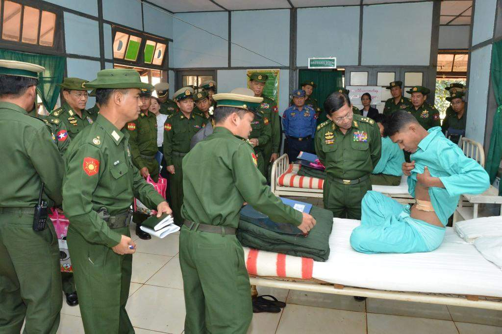 Commander-in-Chief of Defence Services Senior General Min Aung Hlaing comforts a soldier who sustains injuries in the fight against Kokang  renegade troops.—Myawady