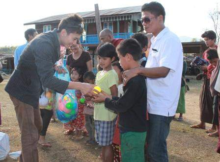 A philanthropist presents gifts to children  from a refugee camp.