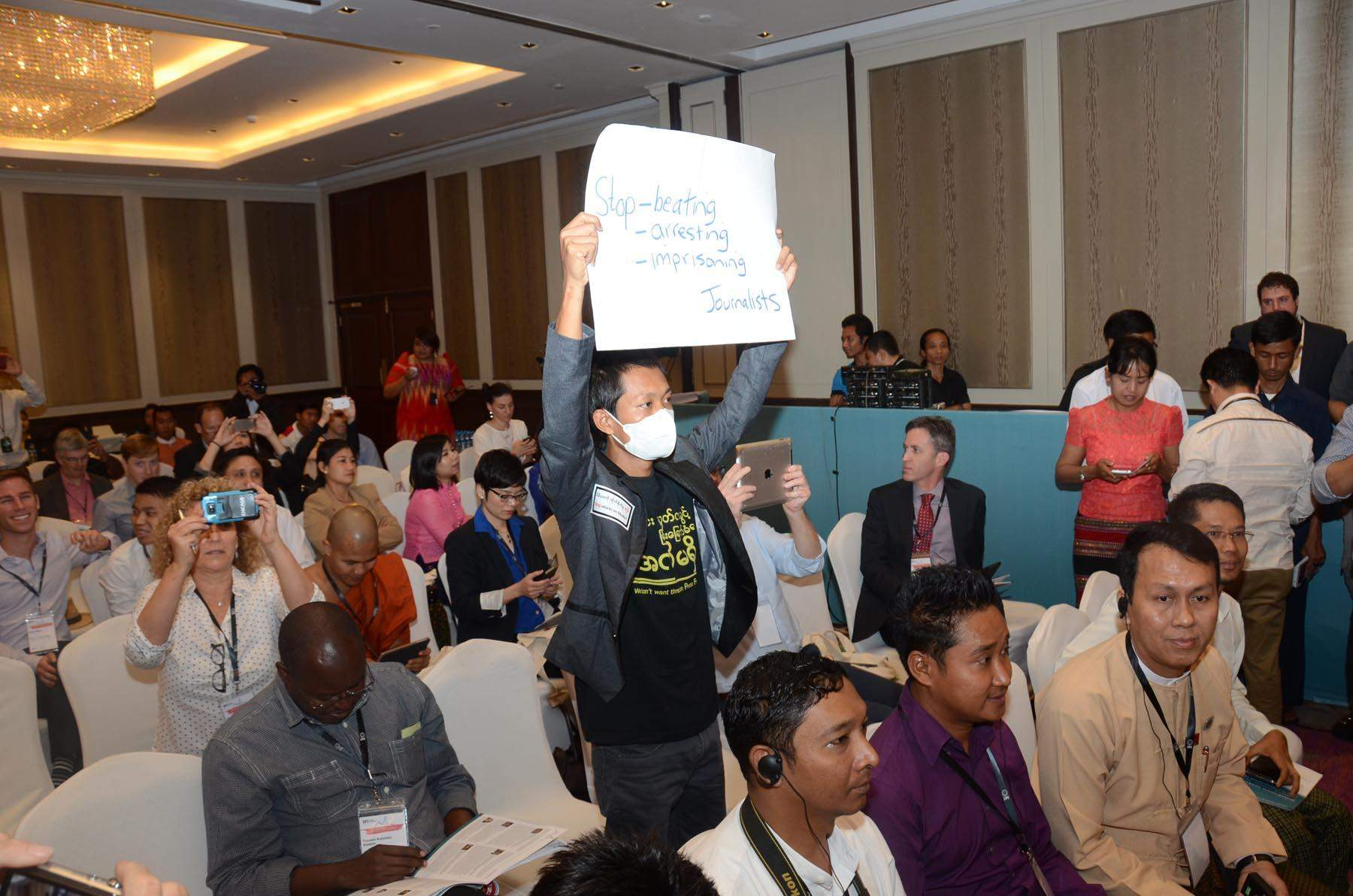 A journalist in protest calling for freedom of expression at IPI World Congress.
