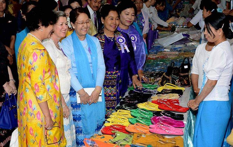 Honorable patron of MWAF Daw Khin Khin Win views products displayed by women's vocational trainng schools.—mna