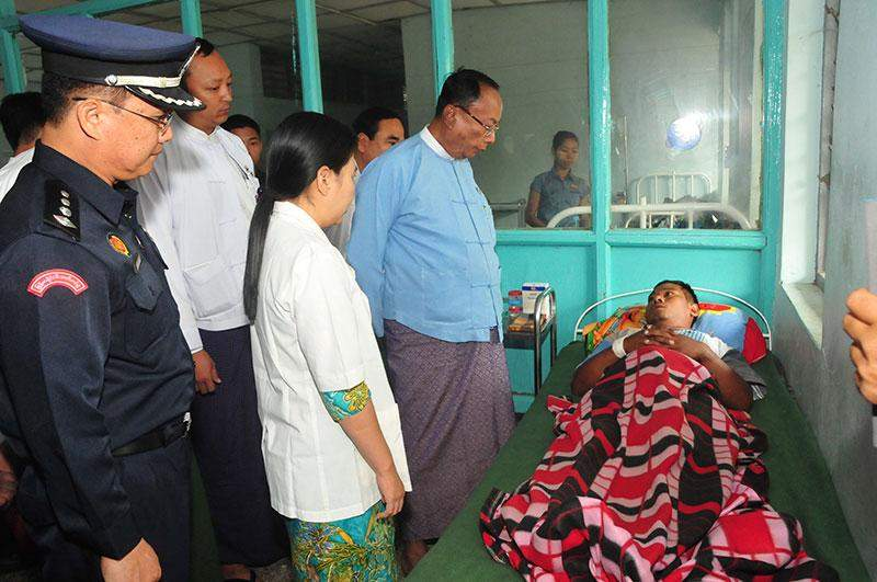 Speaker U Khin Aung Myint comforts patient at station hospital in Thazi Township.—MNA