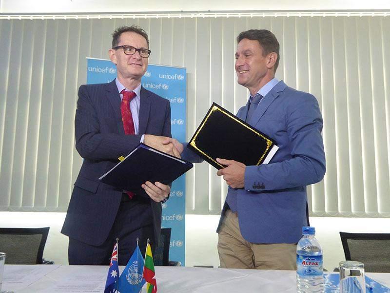 Mr Nicholas Coppel, Australian Ambassador to Myanmar, (left), and Mr Bertrand Bainvel, UNICEF Representative to Myanmar, exchange notes of agreement on child protection programmes.—By Khaing Thanda Lwin