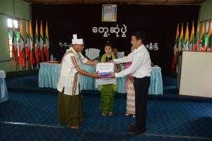 Union Minister  U Ye Htut presents gifts to a local resident in Hkamti.