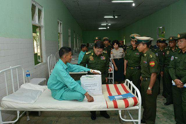 Commander-in-Chief of Defence Services Senior General Min Aung Hlaing comforts a patient soldier at military hospital in Sittway.