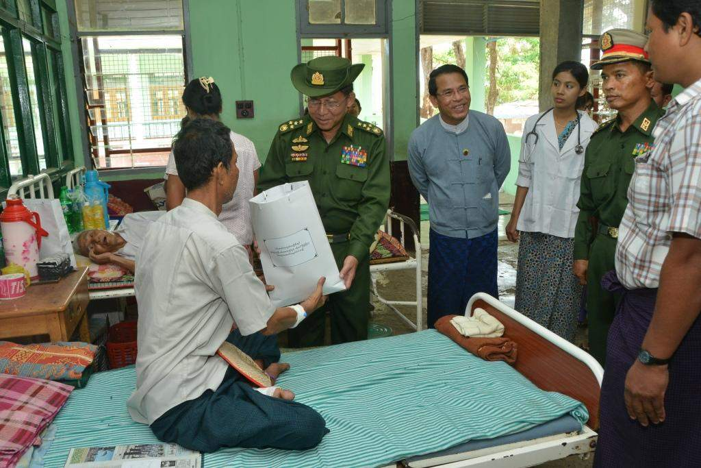 Senior General Min Aung Hlaing presents gifts to a patient at Thandwe District General Hospital.