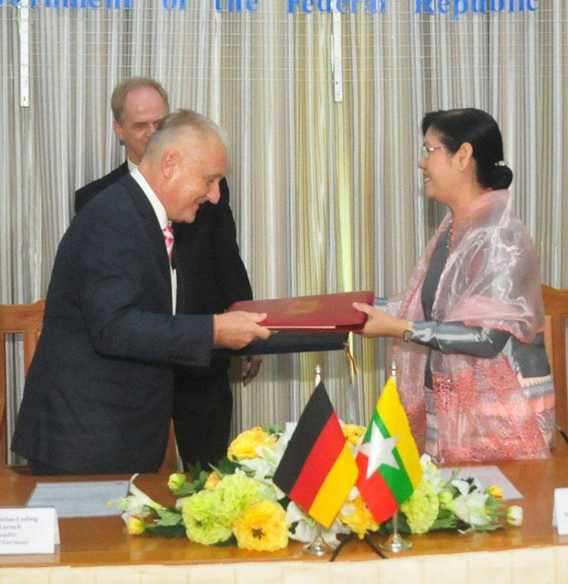 Deputy Minister Daw Lei Lei Thein and German Ambassador Mr Christian Ludwig Weber-Lortsch exchange notes of agreement on cooperation in development.