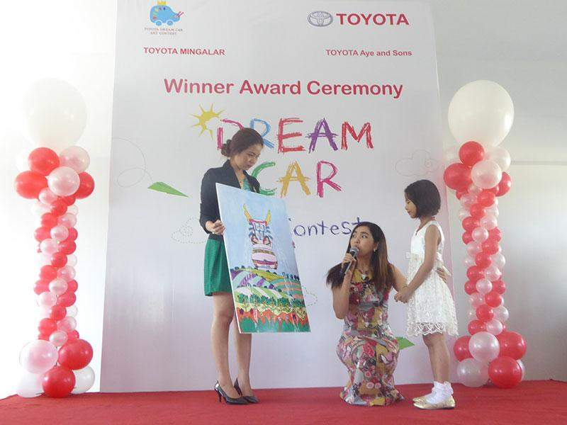 Chuu Thantha Kyaw, 7, receives a second-place prize in the seven and under category of the Toyota Dream Car Art Contest.—Photo: Khaing Thanda Lwin