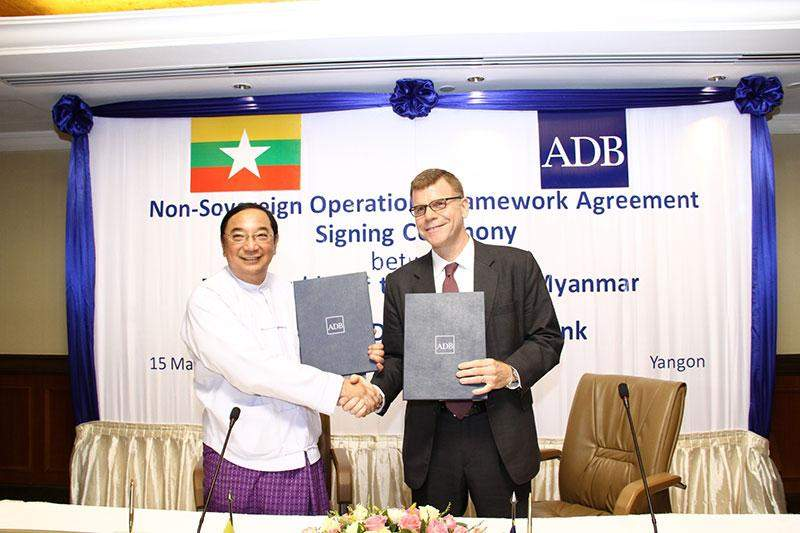 Deputy Minister for Finance Dr. Maung Maung Thein and ADB Vice-President Stephen Groff exchange a handshake after signing a non-sovereign framework agreement that will allow ADB to provide loans, equity investments, guarantees, and trade financing directly to private companies and projects in the country.—Photo: Credit to ADB Myanmar