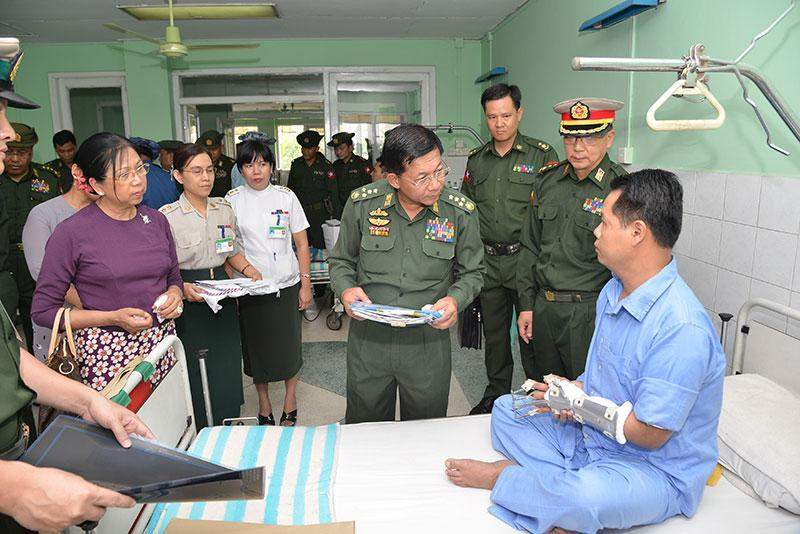 Senior General Min Aung Hlaing and wife Daw Kyu Kyu Hla comfort patient at military hospital in Mingaladon Township.—Myawady