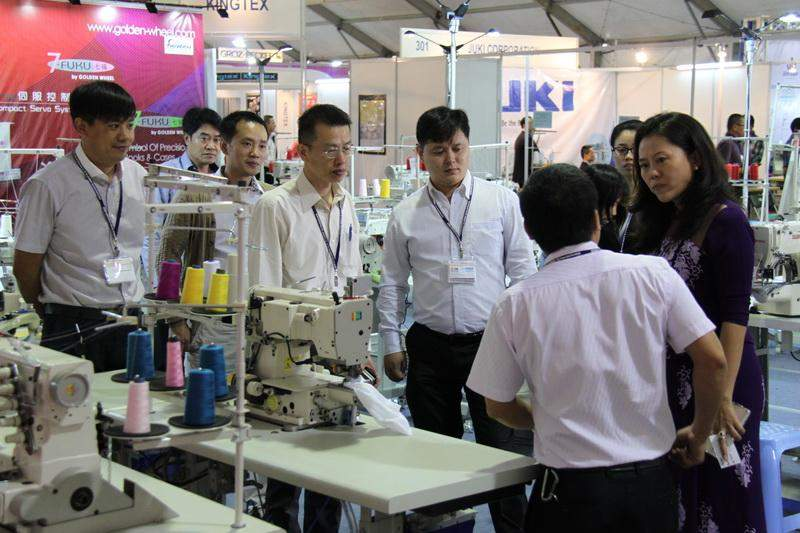 Fair-goers observe garment machinery at the third Myanmar Textile &  Garment Industry Exhibition held in last year's November in Yangon.