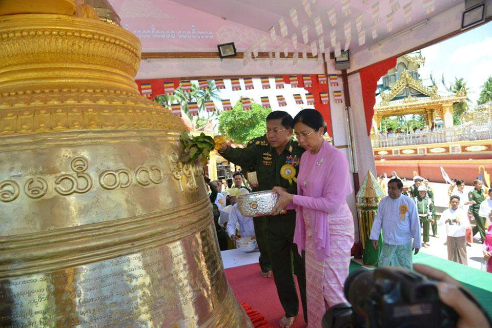 Senior General Min Aung Hlaing and wife Daw Kyu Kyu Hla sprinkle scent water on the bronze bell.