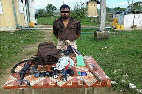 An arrested man wearing uniform of foreign  security force seen with firearms and  ammunition.