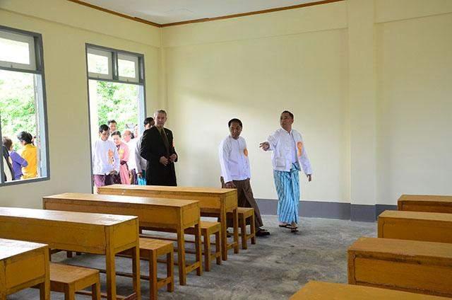 Yangon Region Chief Minister U Myint Swe looks around a new classroom in Htantabin Township.