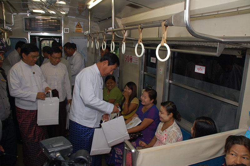 Union Minister U Than Htay and Union Minister U Nyan Tun Aung present gifts to passengers on board the air-conditioned train.