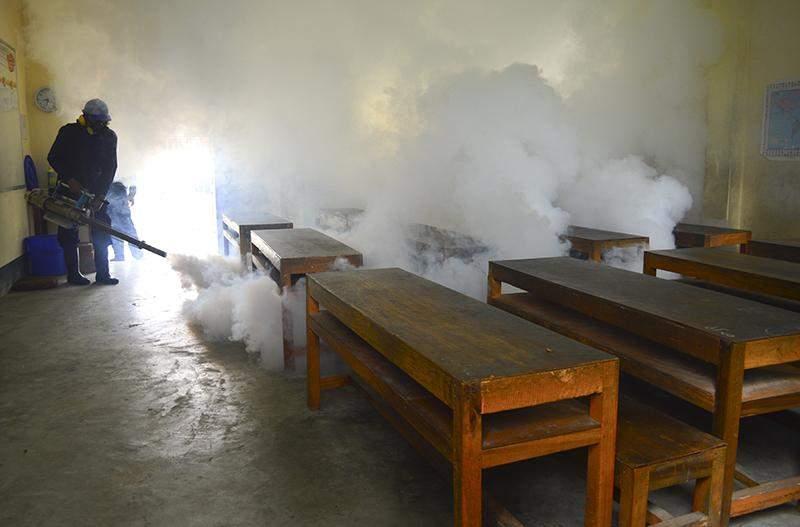 A health staff fumigates a class room in South Okkalapa Township on 15 July, 2015. Photo: Aye Min Soe