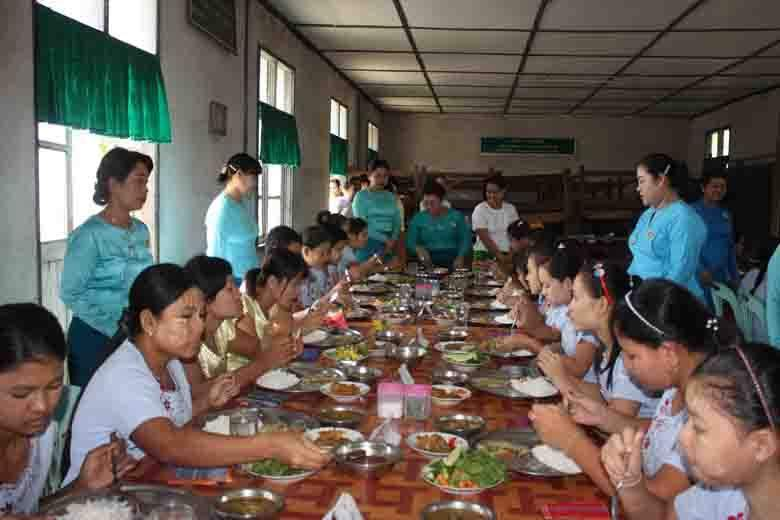 Myawady District Women's Affairs Organization serves lunch to female trainees of tailoring and bikery courses at Vocational Training School for the Women in Myawady, Kayin State, on 3 July. Tun Tun Oo (Myawady Town)