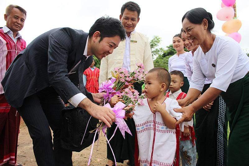 A Kayin child welcomes Mr. Kazuyoshi SUZUKI, Second Secretary of the Embassy of Japan at the school opening ceremony.--Japanese Embassy