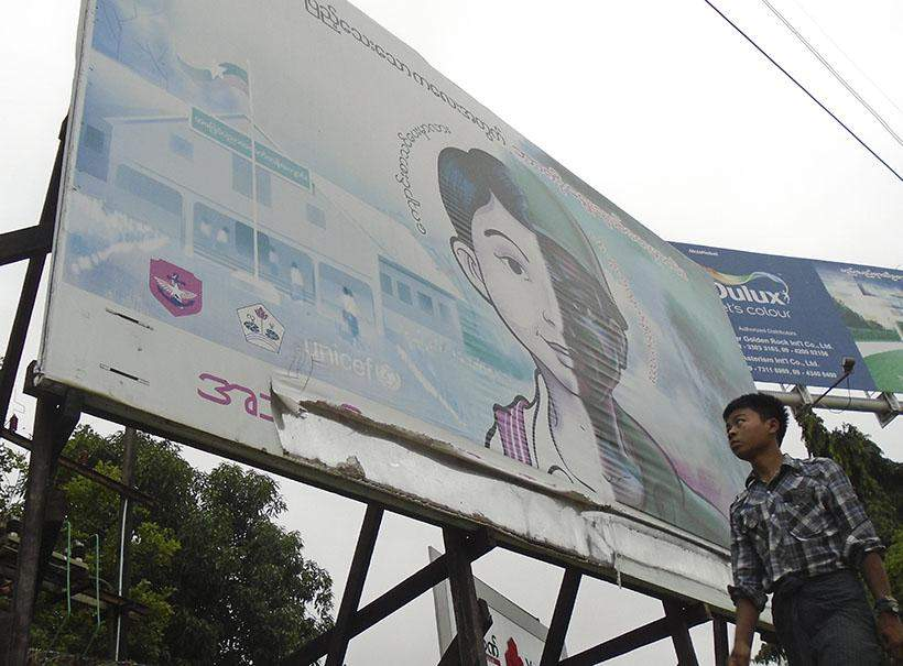 """A young boy walks past a billboard promoting a """"No Child Soldiers""""  campaign in Yangon."""