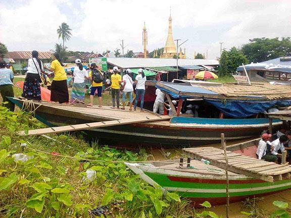 Volunteers relaying donated drinking water and foodstuff to load a boat at  a jetty of U Par Ye Pagoda in Hinthada, Ayeyawady Region.