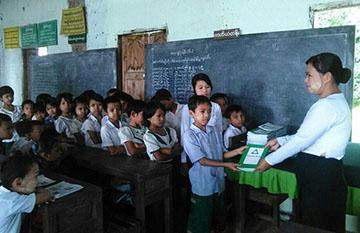 Teacher presents notebooks to students at Kwetanshay BEMS Branch in Bago.