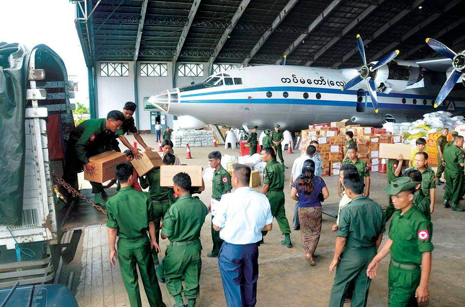 Military personnel loading aid items onto an air force plane to ship them to flood-hit areas.