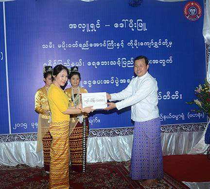U San Shwe Aung, permanent secretary of the Ministry of Border Affairs, accepts cash assistance for flood victims donated by donor Daw Poe Phyu and family.