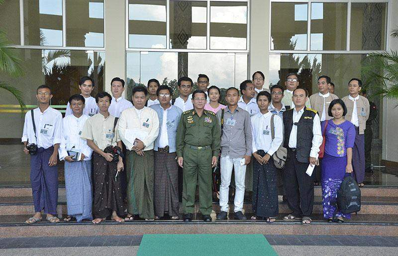 Senior-General Min Aung Hlaing and journalists have photos taken together outside Bayintnaung Hall of the military command. Photo: MNA