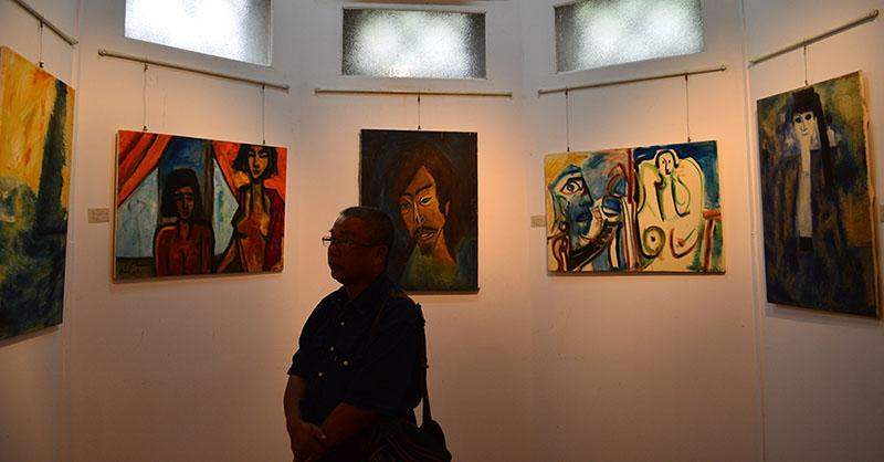 A visitor looks at art works of Kin Maung Yin at Gallery Sixty Five.