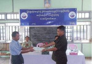 An official presents cash assistance fund to a local in Myingyan District. Photo: Zaw Myint Naing