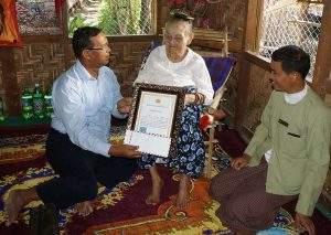 Mandalay Region transportation minister U Kyaw San presents honorarium from president to a centenarian in Meiktila. Photo: Chan Tha