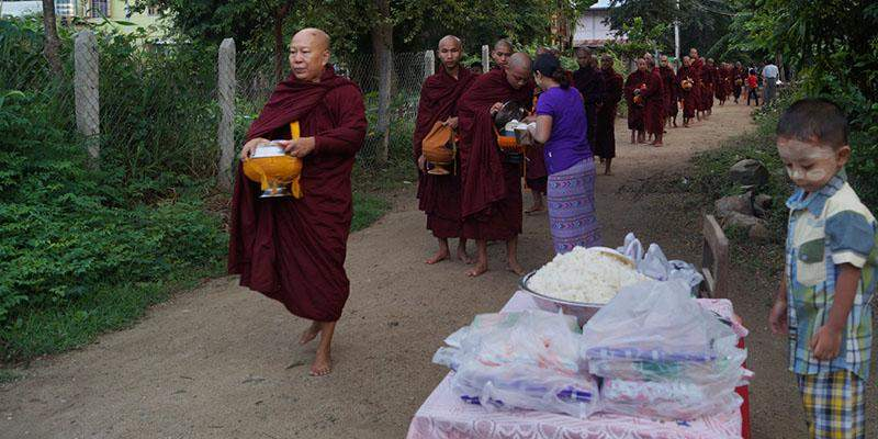 Buddhist monks receive alms from people in Tatkon during the 16th annual alms event in Tatkon.