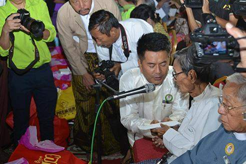 Myanmar Motion Pictures Organisation Chairman U Lu Min presents gifts to an elder motion picture artist.