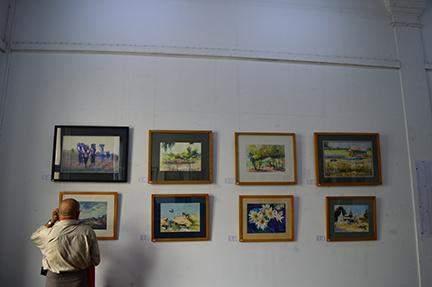 A visitor enjoys art works of (U) Mya Thaung at Lokanat Galleries.