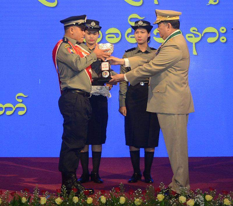 Union Minister Lt-Gen Ko Ko presents an award to an outstanding police at a ceremony to mark Myanmar Police Force Day. Photo: MNA