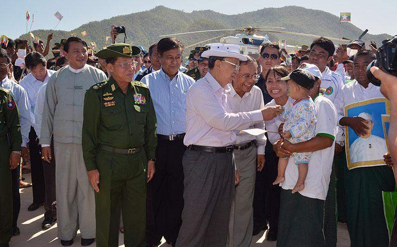 President U Thein Sein talks to a local mother and a child during his tour of Myogyi Dam.