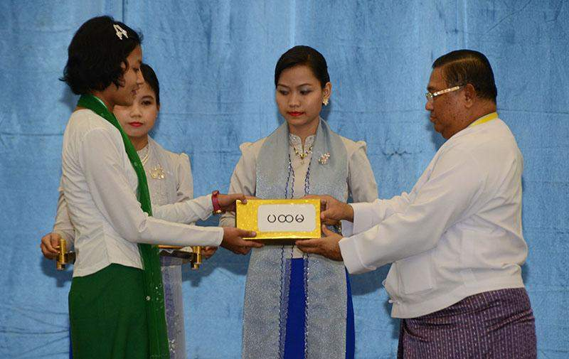 Union Minister for Foreign Affairs U Wunna Maung Lwin presents award to a student at the ceremony to mark United Nations Day. Photo: MNA
