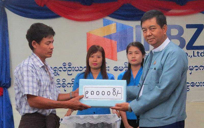 An official from IKBZ hands over compensation to injured passenger. Photo: KBZ