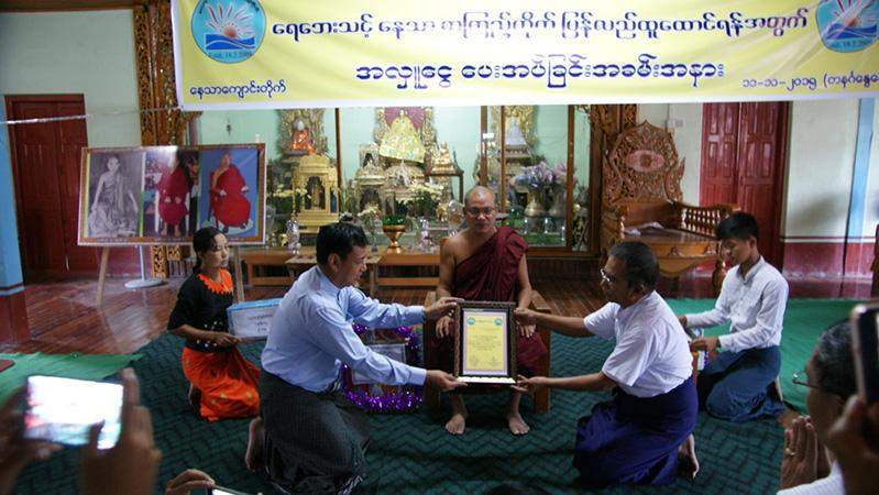 Union Minister U Ye Htut accepts certificate of honour for donation for library.