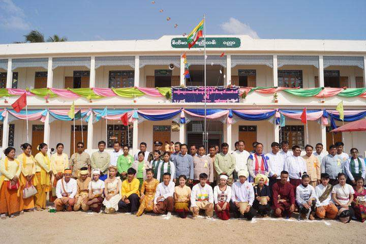 Attendees pose for documentary photo at the opening ceremony of the new two-storeyed building.